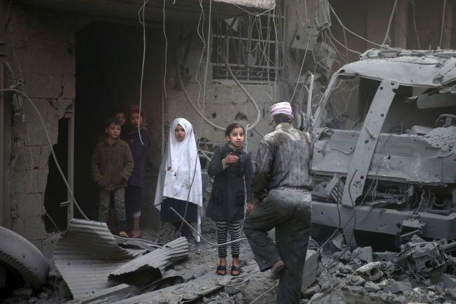 DOUMA: Barn ser på skadene etter det aktivister sier er luftangrep utført av russiske styrker i den syriske byen Douma ikke langt unna hovedstaden Damaskus den 10. januar i år.