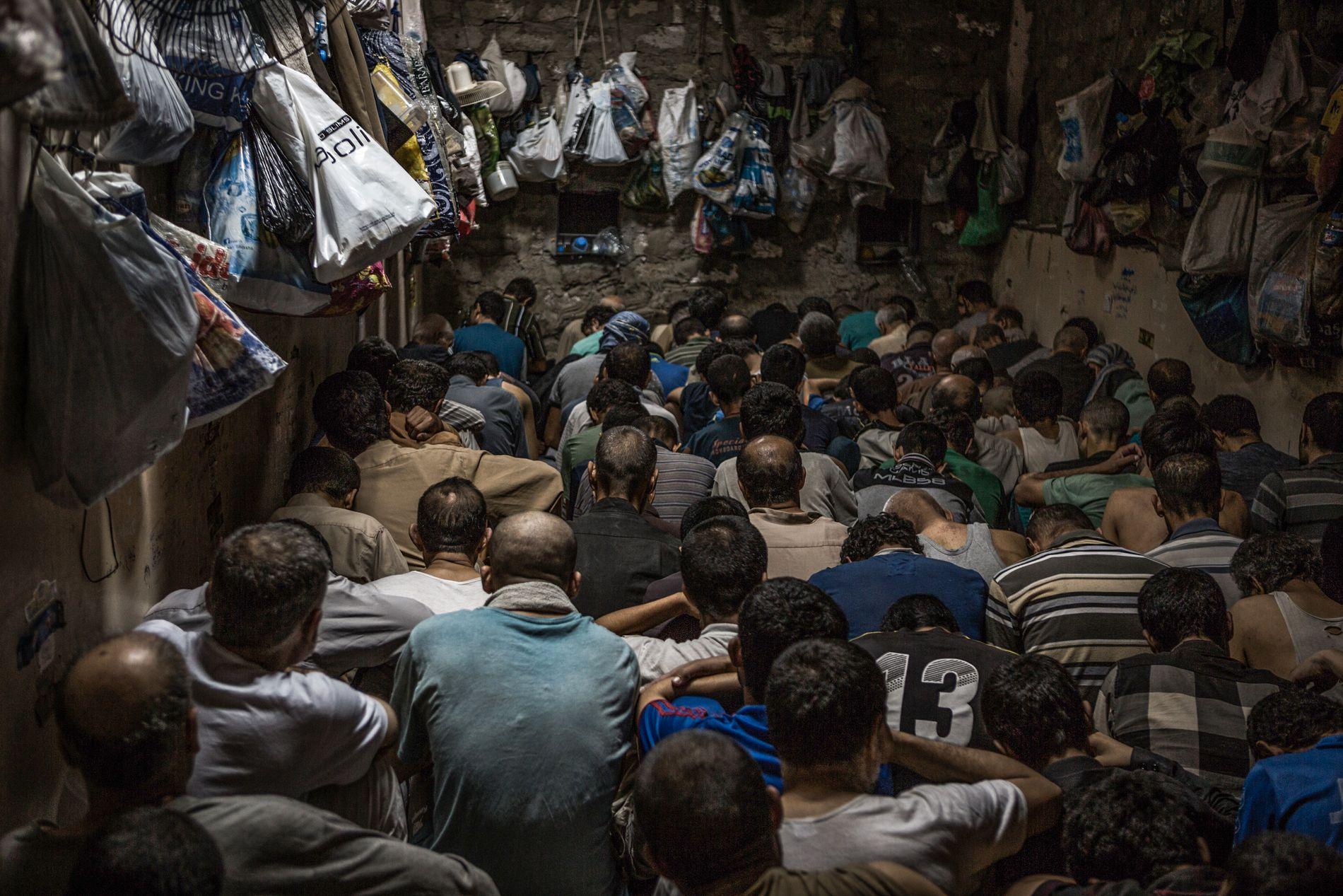 FENGSLET: IS-mistenkte menn sitter varetektsfengslet i en kjeller ved Mosul. Flere holdes der i ukevis. De må sove sittende, og deres eiendeler henger i plastposer på veggen. Bildet er tatt 7. juni i år.