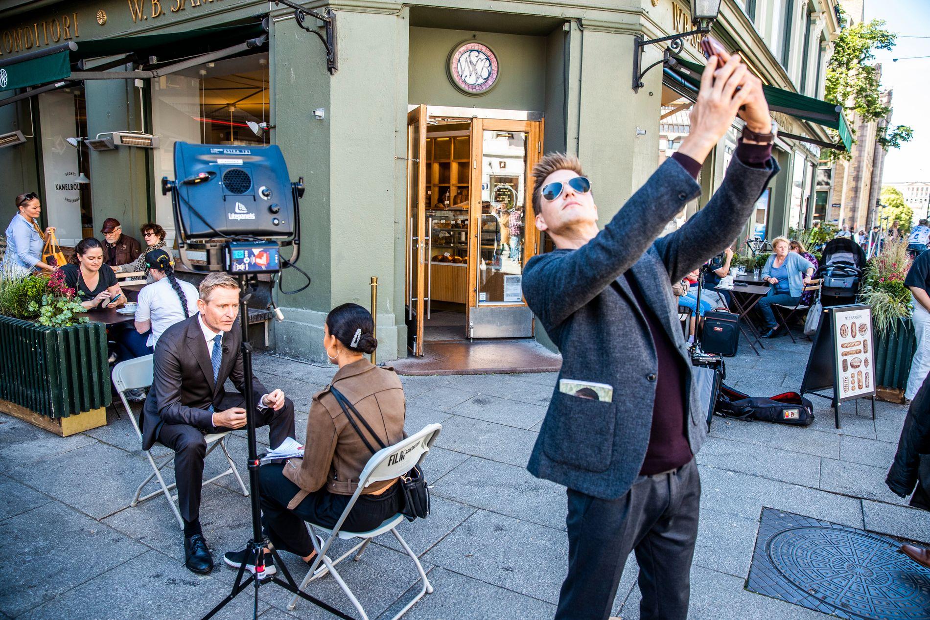 RIVALER: Mads Sjøgård Pettersen tar selfie mens Mestad blir intervjuet i bakgrunnen. Han spiller Jesper Bergs valgkamputfordrer, Petter Bjørnstad. – Problemet er at jeg hadde stemt på ham selv, sier Pettersen og peker på Mestad.