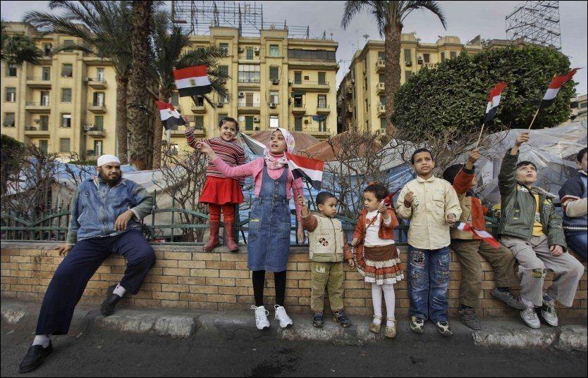 BARN DEMONSTRERER: Barn veiver med det egyptiske flagget på Tahrir-torget i Kairo onsdag. Demonstrasjonene er nå også i ferd med å spre seg til landsbygda. Foto: AP