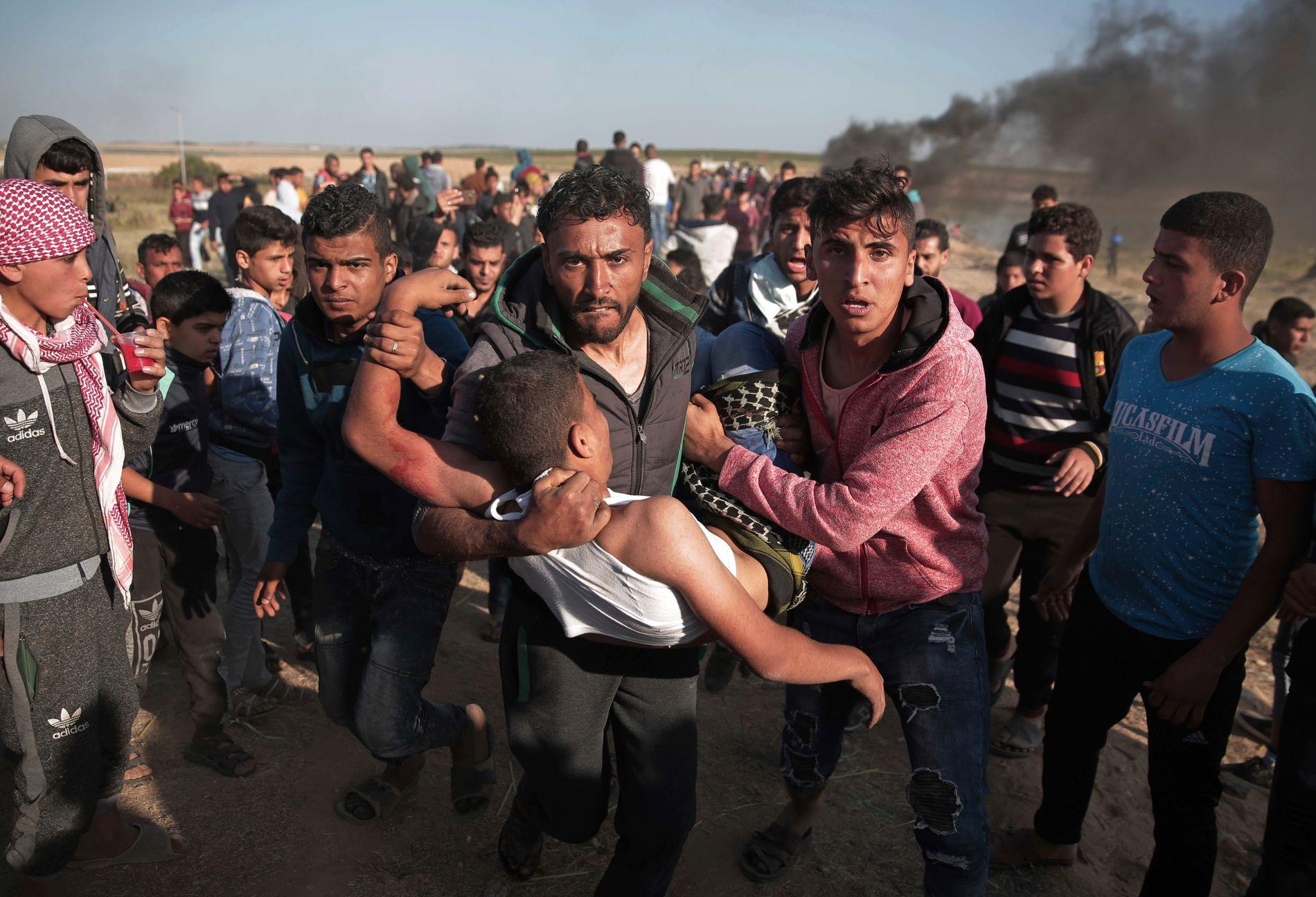 Palestinske demonstranter bærer bort en mann som ble skutt av israelske soldater under protester øst for Gaza by lørdag.