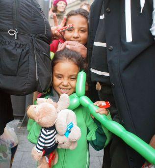 FIKK GAVER: Disse to syriske jentene fikk ballonger og bamser av ukjente mennesker som hadde møtt opp på jernbanestasjonen i München lørdag, for å ønske flyktningene velkommen.