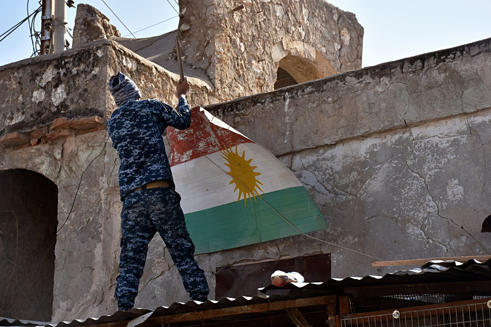 SYMBOLSK: En irakisk soldat fjerner et kurdisk flagg i Altun Kupri. Myndighetene i Bagdad hever nå å ha kontroll over den strategisk plasserte landsbyen.