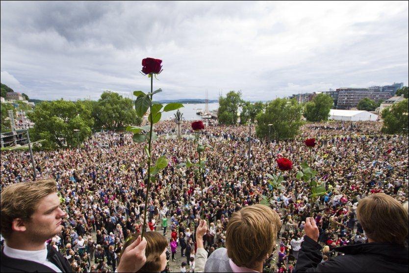 ROSEHAV: Over 150.000 mennesker løftet roser i luften mens de sang «Ja, vi elsker» i Oslo sentrum mandag kveld. Foto: Scanpix