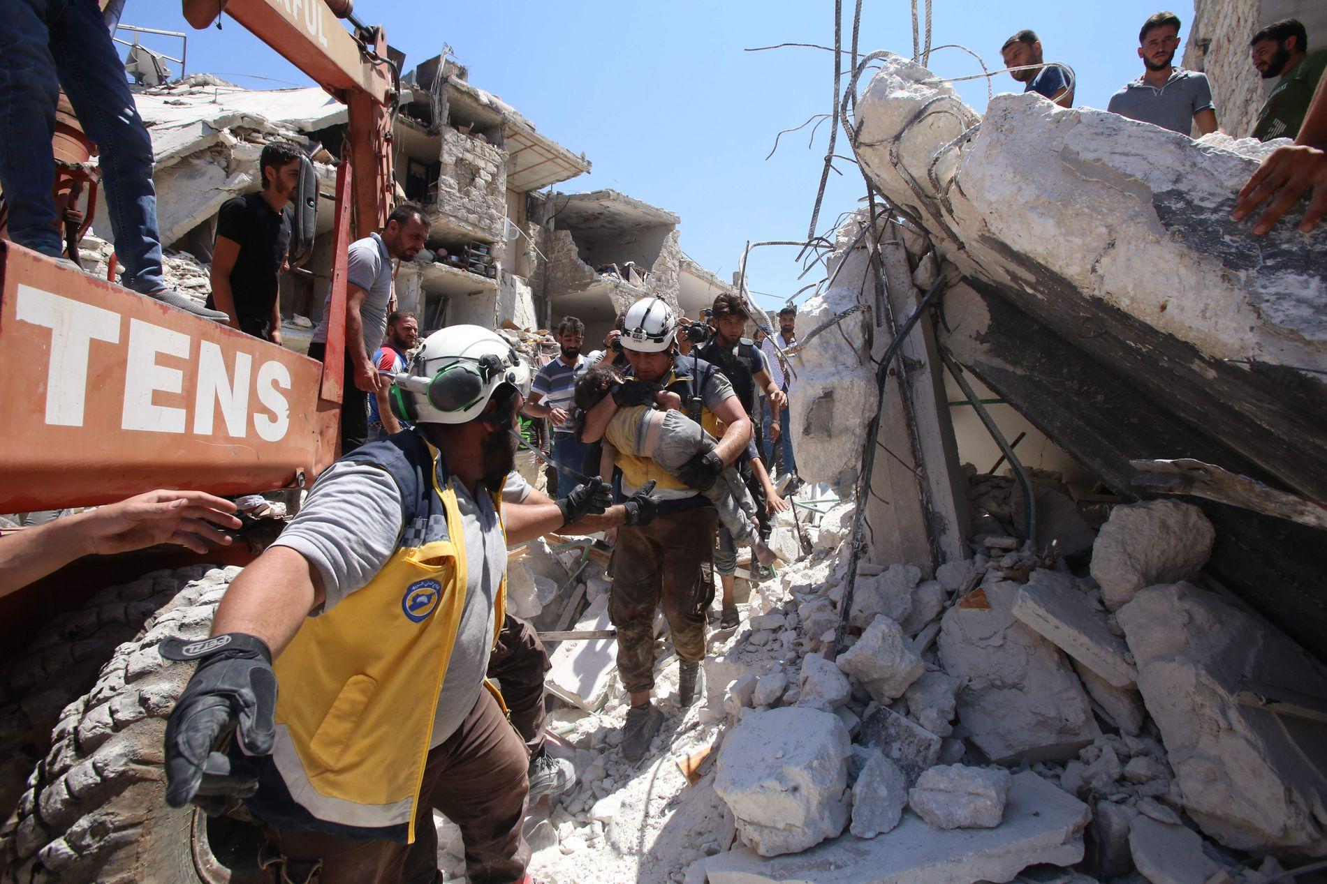 KRITISERES OG REDDER LIV: Redningsarbeidere i «De hvite hjelmene» evakuerer et skadet barn etter et bombeangrep den 7. juni. Tilhengere av det syriske regimet kritiserer livredderne fordi de operer i et område kontrollert av jihadister.