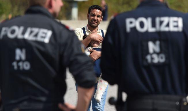 SKJERPER KONTROLLEN: En syrisk far bærer barnet sitt på grensen mellom Østerrike og Ungarn.