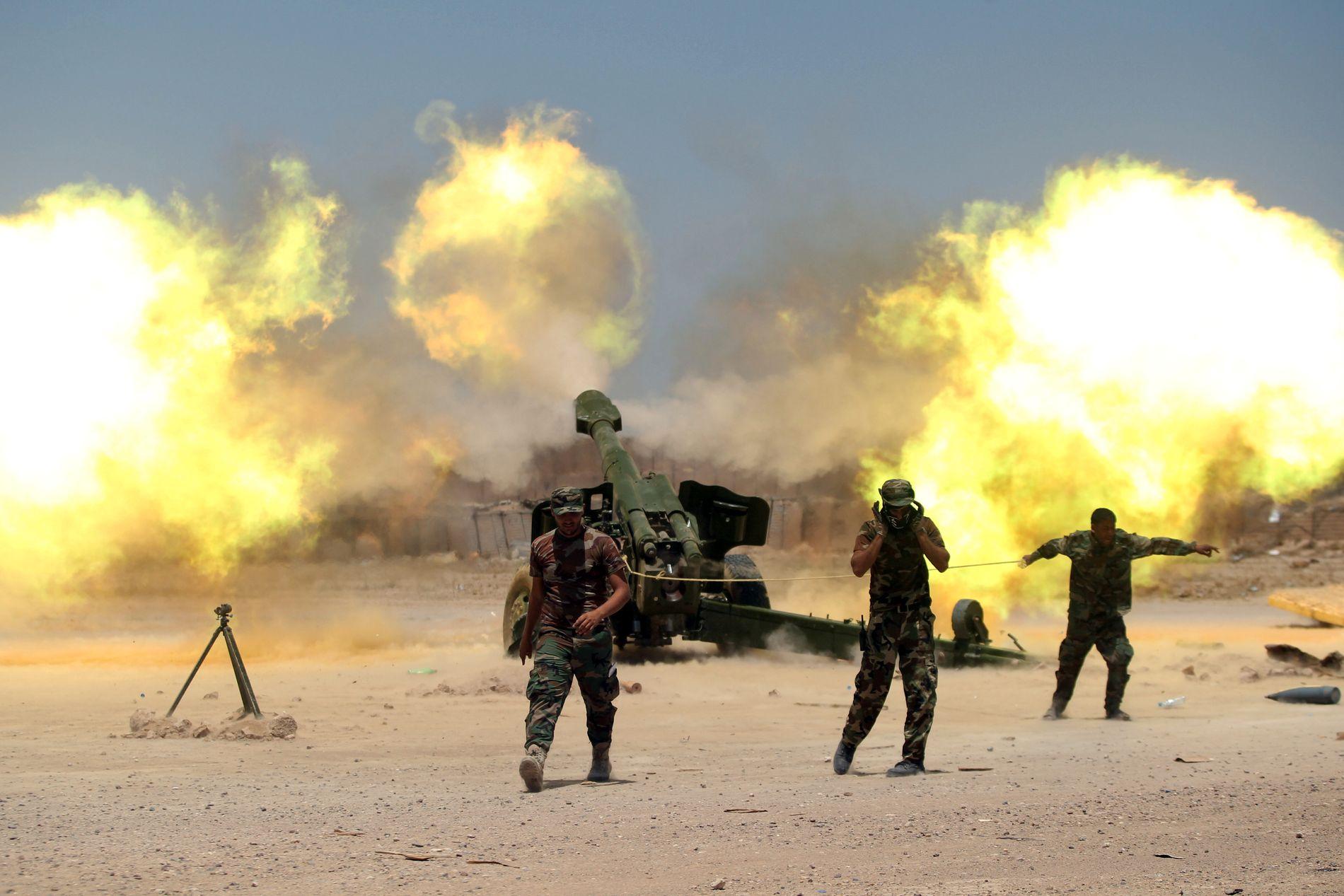 KAMPER: Sjiakrigere og irakiske regjeringsstyrker avfyrer artilleri i kamper mot IS nær Falluja søndag. Foto: REUTERS/Alaa Al-Marjani