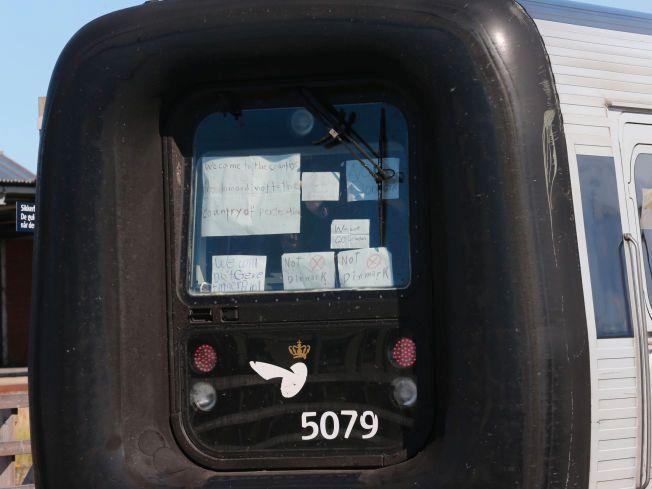 BESKJEDER: Flyktningene på et av togene som ankom Rødby onsdag holdt opp lapper hvor de ga uttrykk for at de ikke ønsker å bli registert i Danmark.