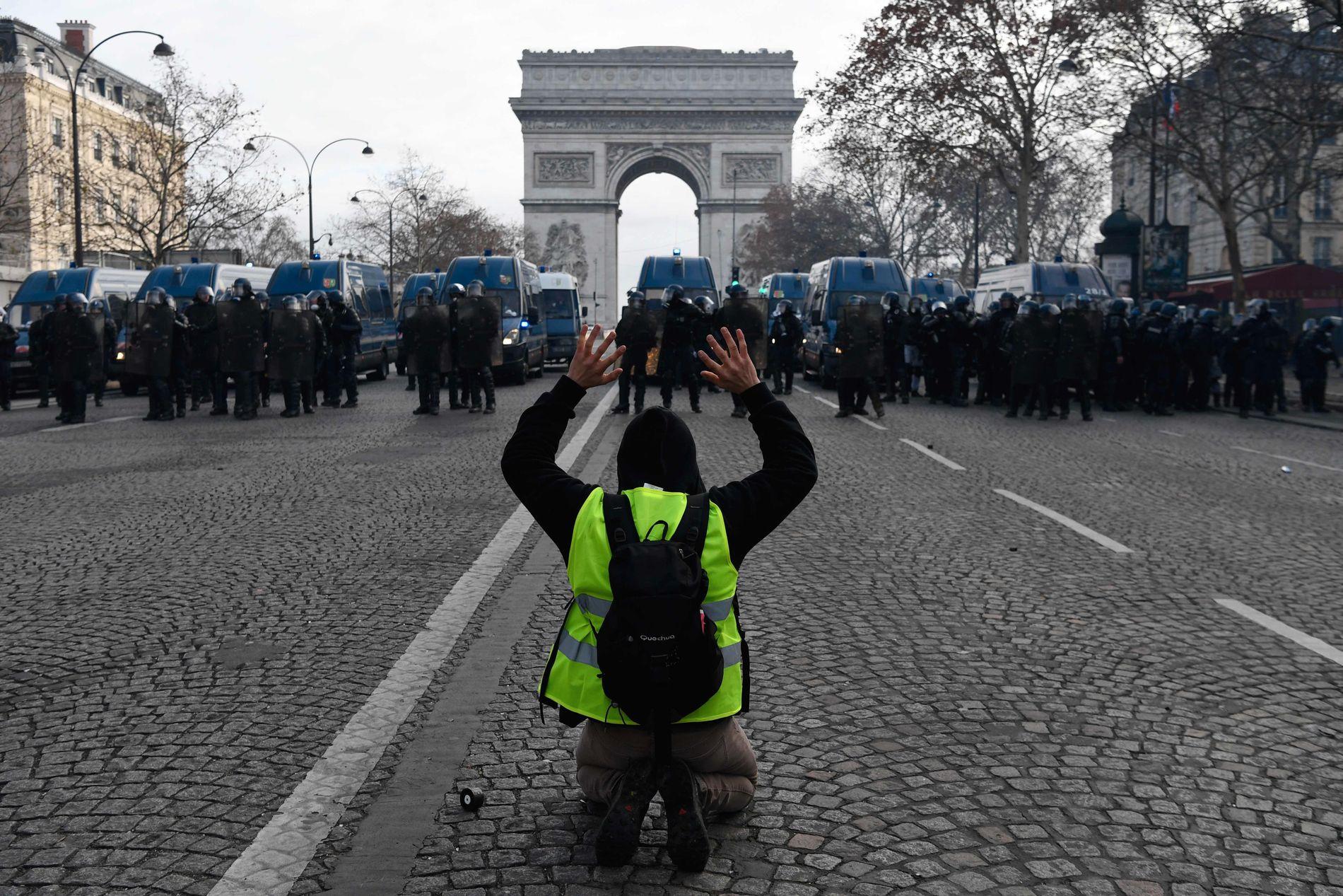 OVERMANNET: En demonstrant fra «de gule vestene» går i knestående i møte med politiet på Champs Elysees i Paris.