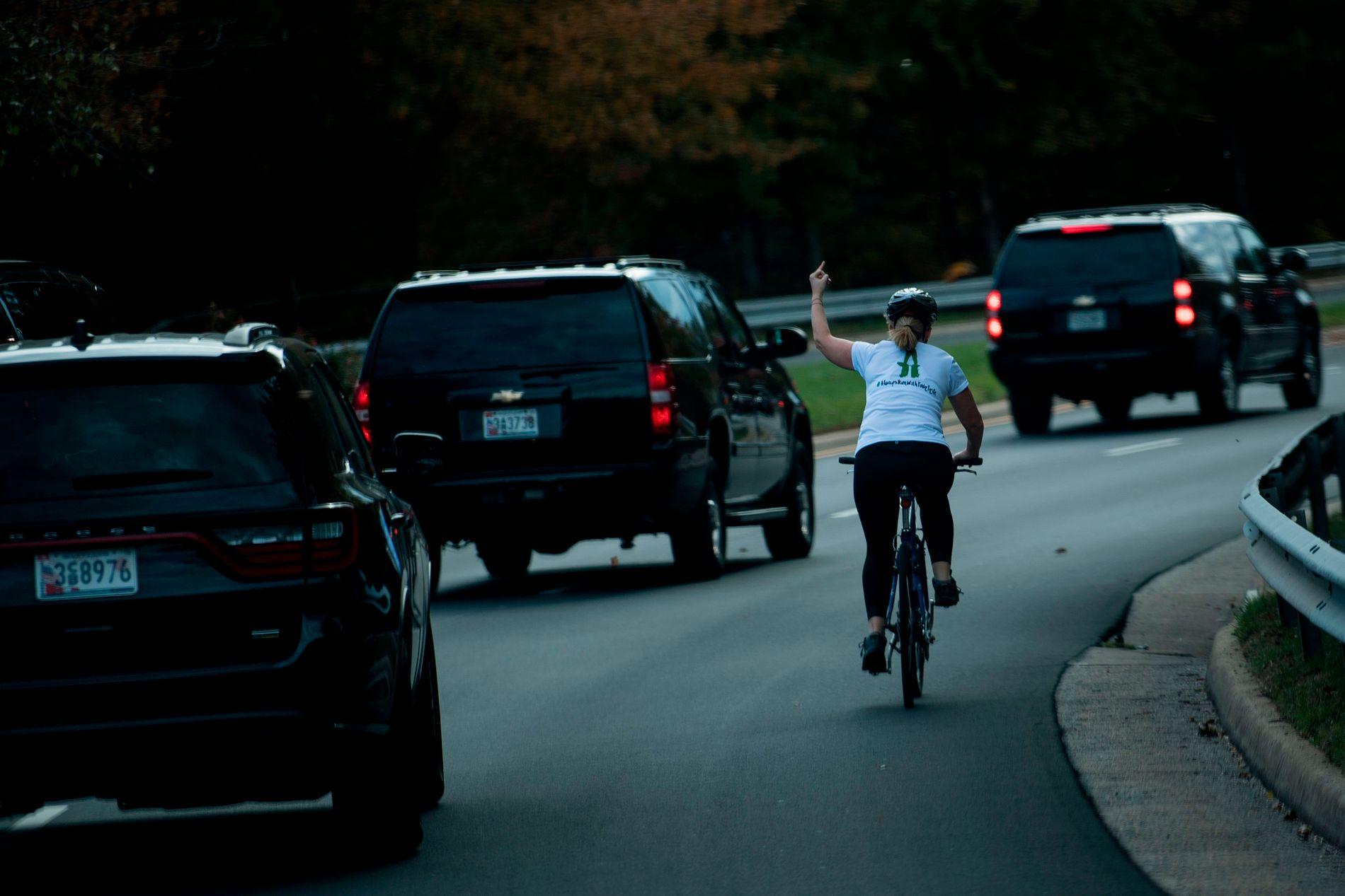 KLAR TALE: Mens Donald Trumps kortesje er på vei fra golfklubben Trump National i Sterling i Virginia, gjør Juli Briskman det klart hva hun synes om presidentens innsats. Hun skal også ha vist fingeren enda en gang til kortesjen. Foto: Brendan Smialowski, AFP