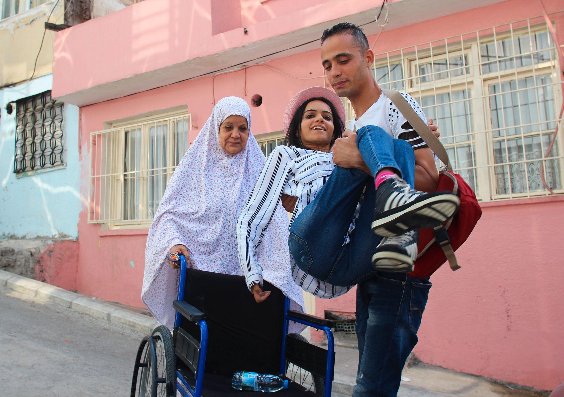 BÆRES INN: Ahmad og moren hjelper Noor inn etter en lang dag. Hun er den eneste i familien som har klart å skaffe seg jobb i Tyrkia.