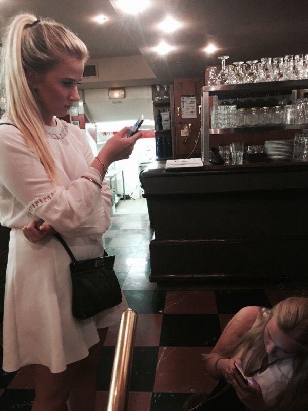 GJEMTE SEG: Martine Elise Hansen (t.v) og søsteren Amalie Christine Hansen gjemte seg sammen med familien i en restaurant. De fulgte med på oppdateringer på situasjonen fra mobiltelefonene sine.