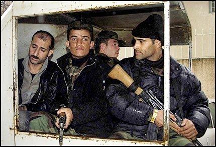 FØRES BORT: Med dødsdommen hengende over seg ble den drapsdømte Osman Omar Osman (t.v.) kjørt vekk fra rettssalen på lasteplanet til en åpen pickup, omringet av væpnede vakter. Foto: OLE DAG KVAMME