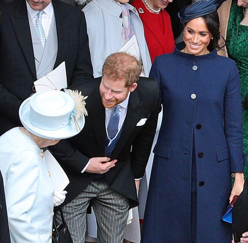 ÅPNE KNAPPER: Hertuginne Meghan hadde kneppet kåpen bare i toppen under fredagens bryllup. Her med prins Harry og dronning Elizabeth.