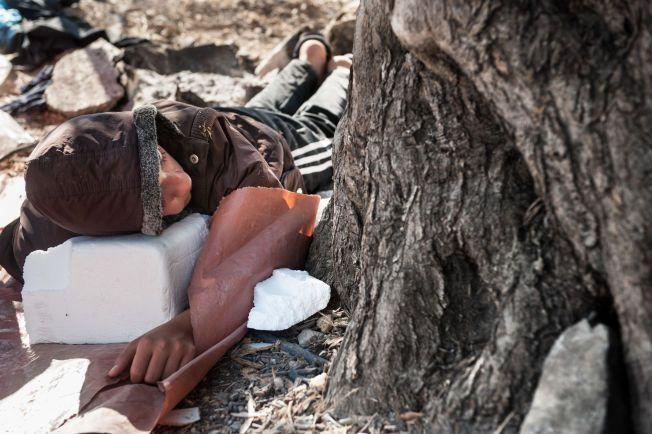 OVERBEFOLKET: Det er ikke plass til alle flyktningene ved de midlertidige oppholdsstedene. Her har en syrisk flyktning lagt seg til å sove under et oliventre i Kara Tepe camp på Lesbos.