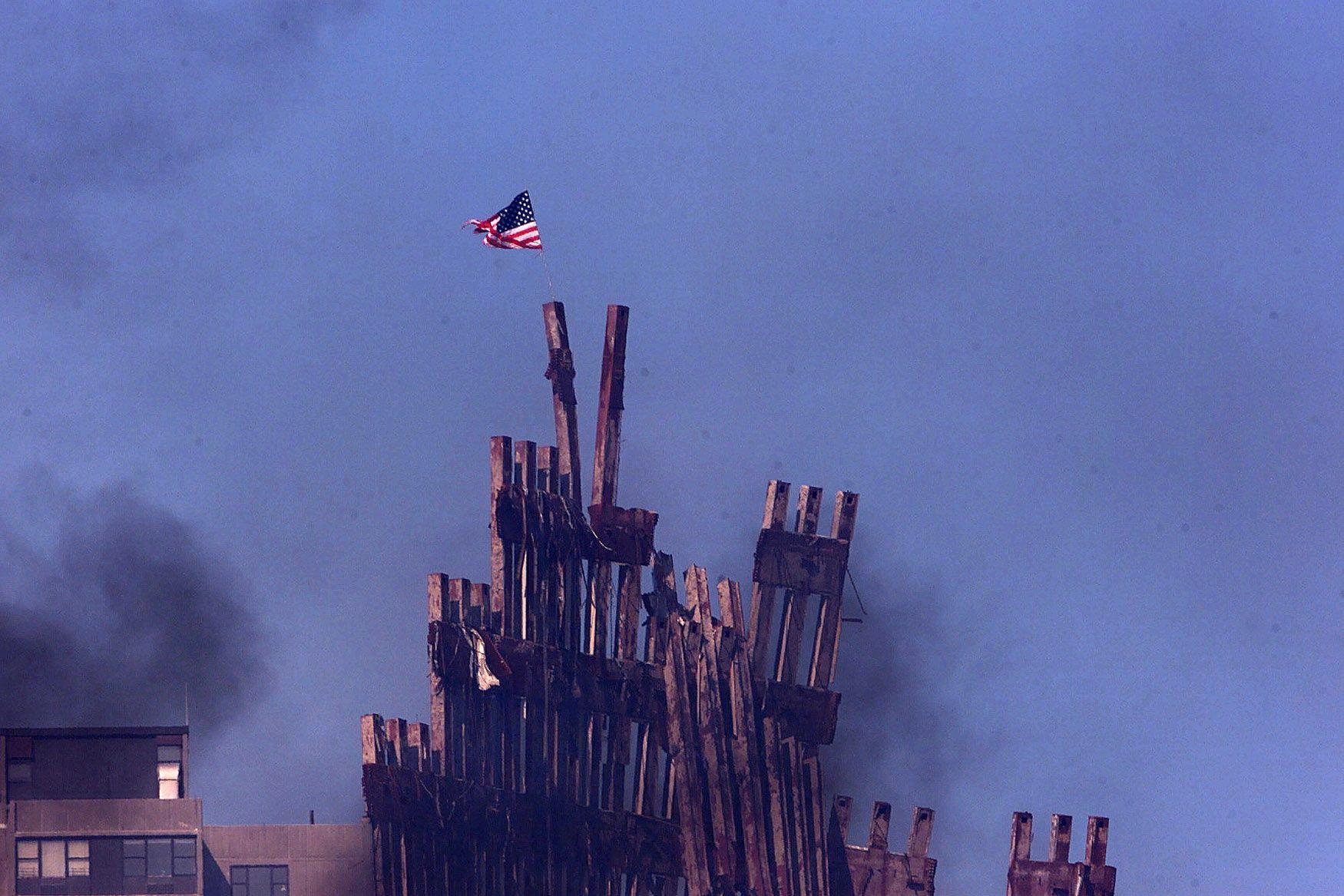 TERRORÅSTED: Ruinene etter de sammenraste tårnene World Trade Center i september 2001. Det amerikanske flagget vaier i toppen.