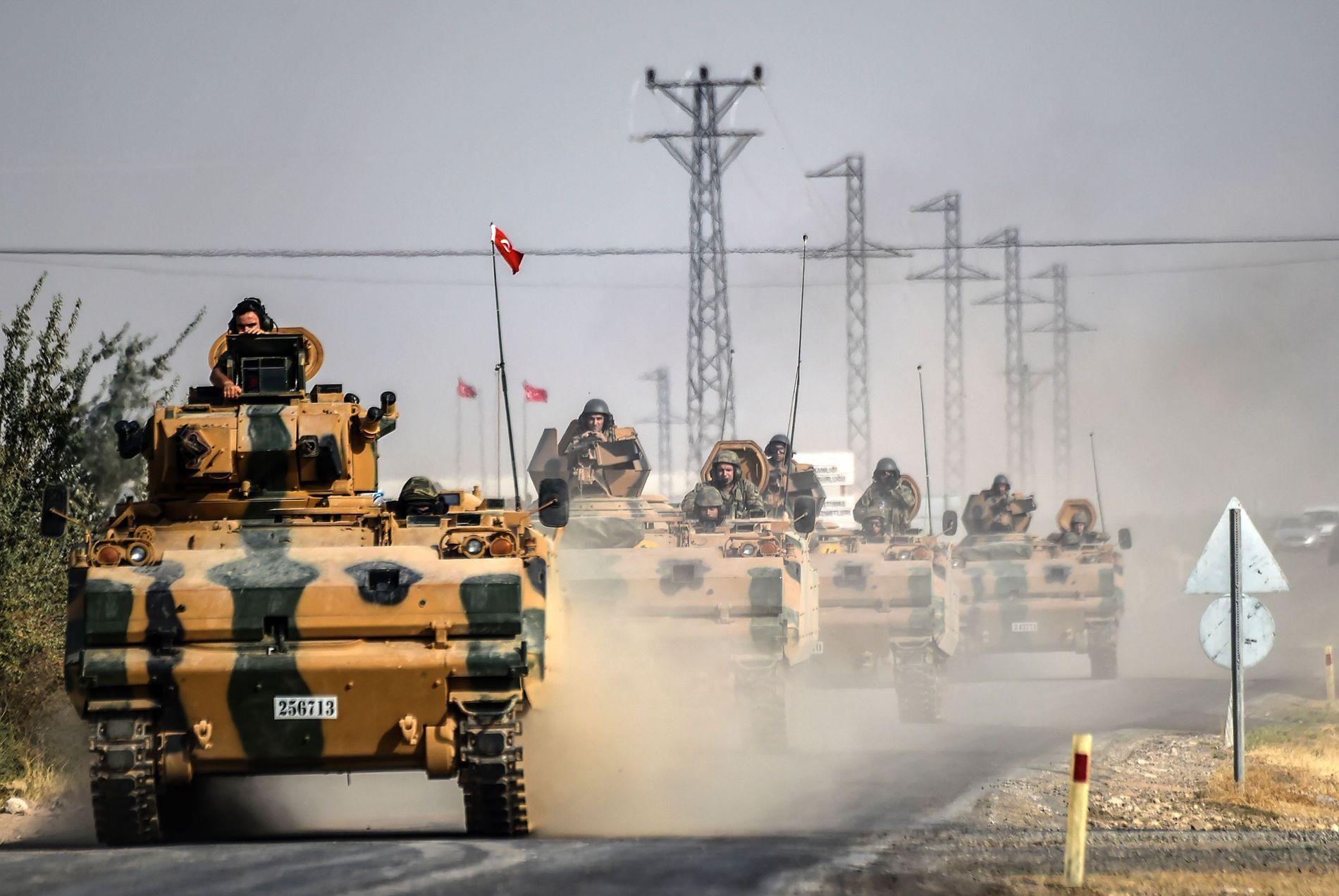 RYKKER FREM: Tyrkiske stridsvogner rykker frem torsdag morgen. Bildet er tatt rundt fem kilometer vest for den tyrkiske grensebyen Karkamis, på vei mot den syriske byen Jarablus, der Tyrkia igangsatte en omfattende offensiv på onsdag.