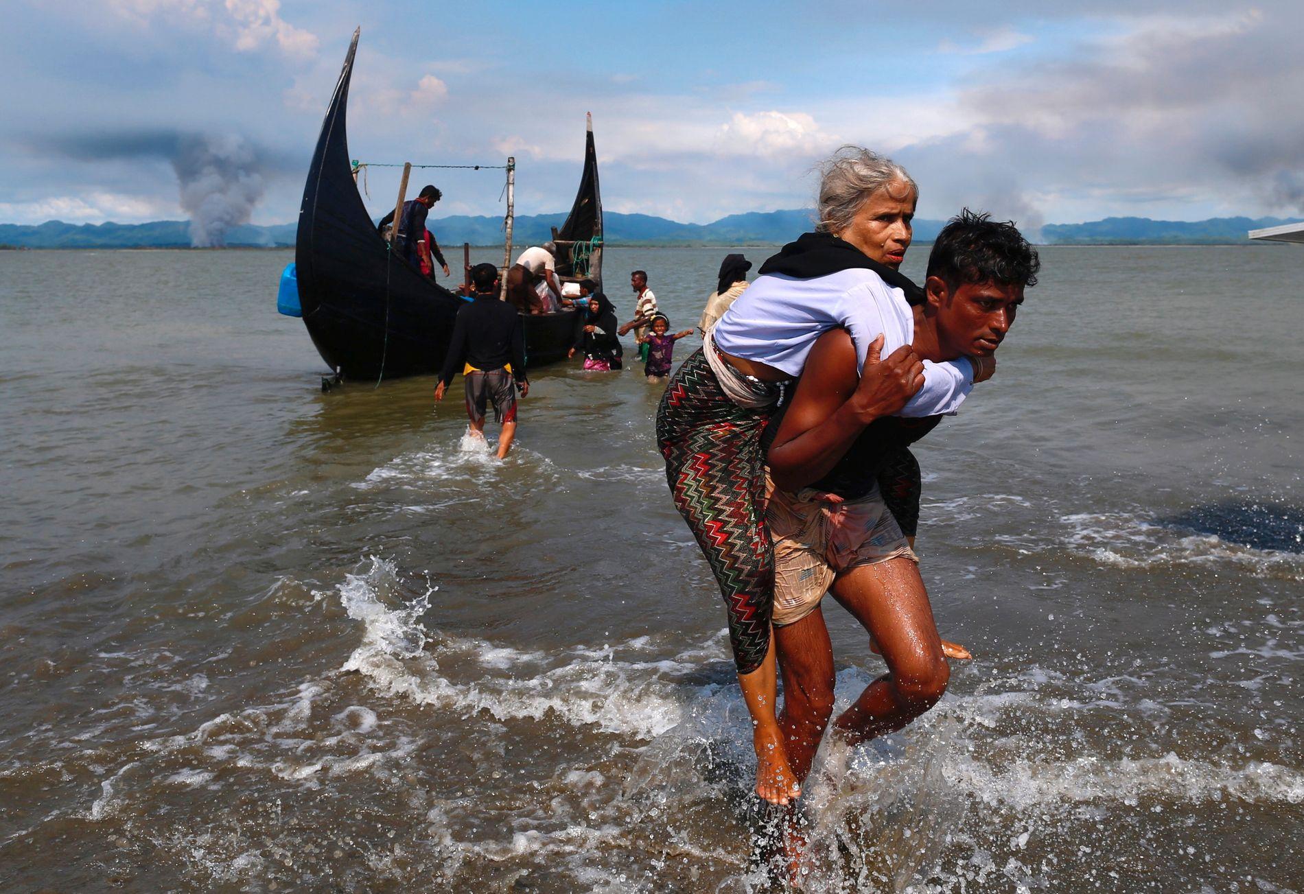 FLYKTER FRA BRENNENDE HJEM: I bakgrunnen, over grensen til Myanmar brenner det. Denne kvinnen klarte å fredag å flykte unna, inn i Bangladesh.