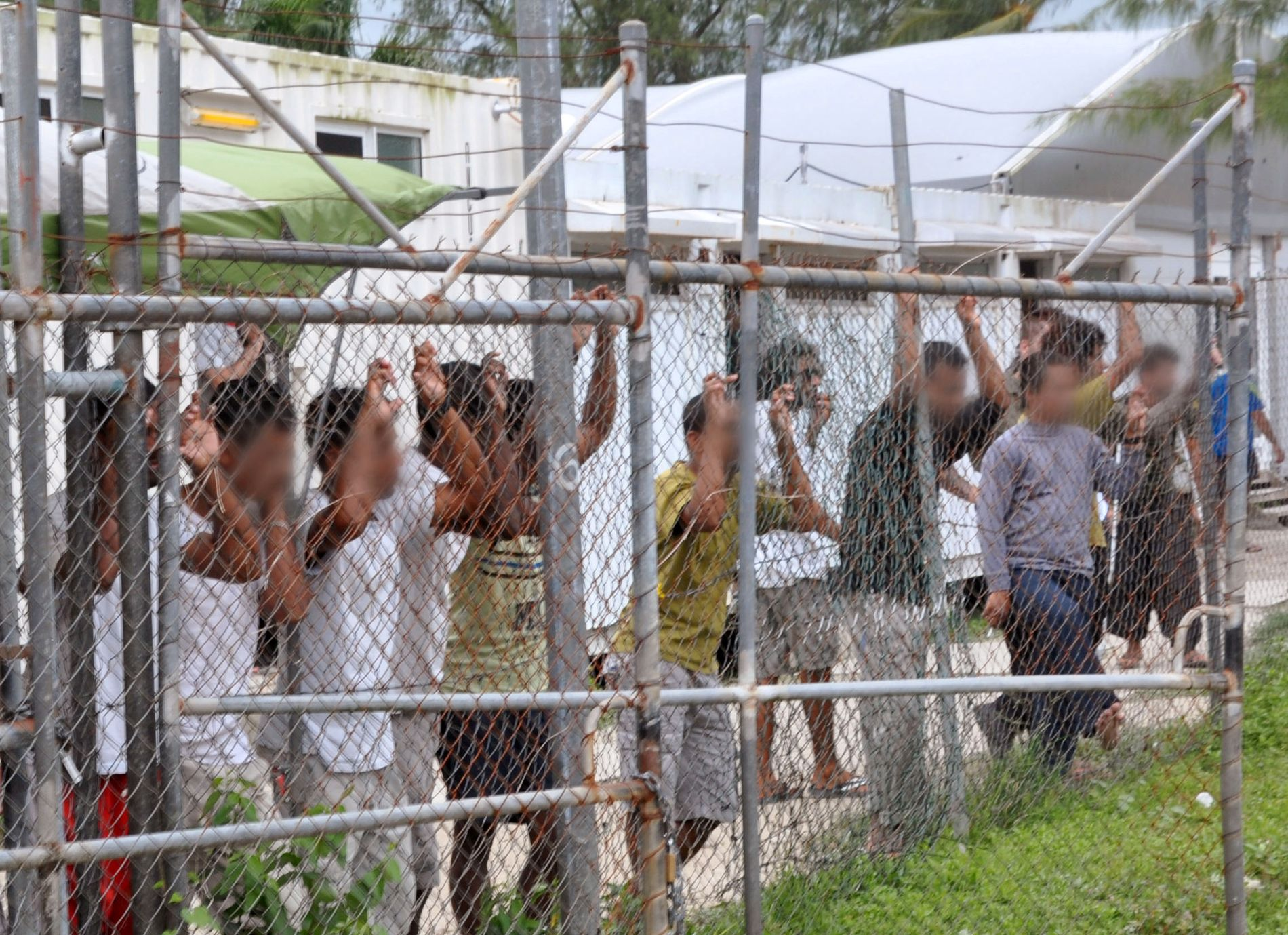 HER SIKRES PENSJONEN DIN: Asylsøkere ser ut gjennom gjerdet på interneringsleiren på Manus-øya i Papua Ny-Guinea. Oljefondet eier aksjer for 2,5 milliarder kroner i selskapet som driver de to mest beryktede leirene.