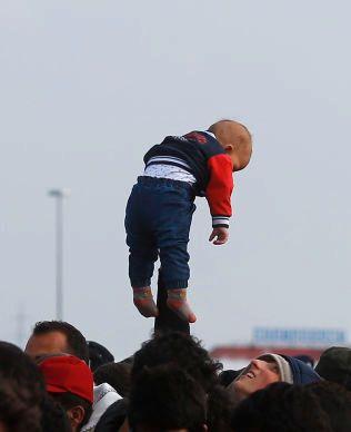 VENTETID: Midt i menneskekaoset holder en mann en liten baby opp i luften i grensebyen Nickelsdorf.