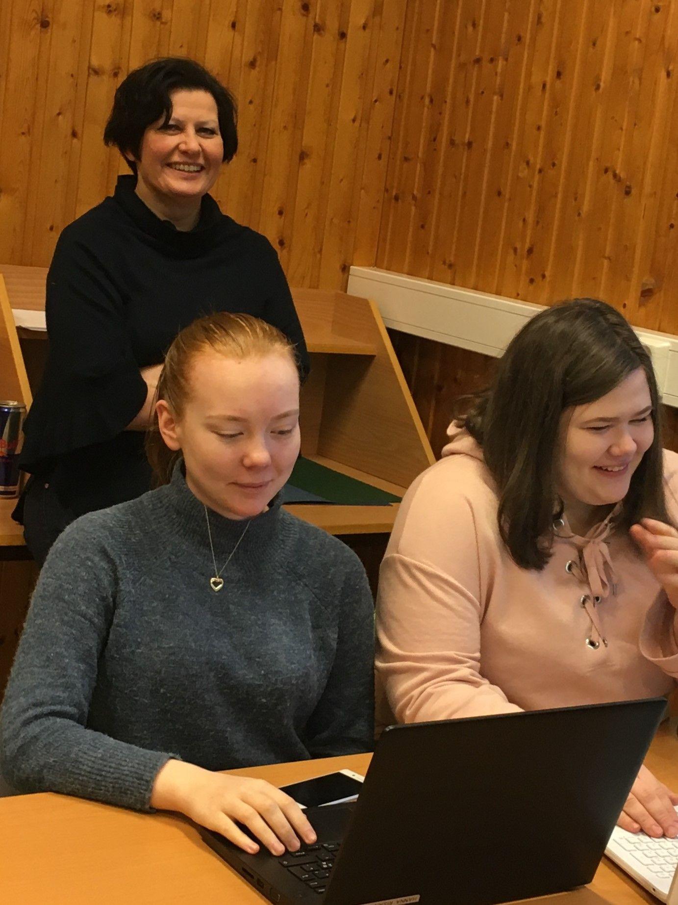 LÆRER: Helga Pedersen liker å undervise i politikk og samfunnsfag på Tana videregående skole. Hun har satt i gang engasjerte diskusjoner om aktuell politikk, og ikke minst metoo de siste månedene. I forgrunnen: Elevene Hanna Risan Andersen (til venstre) og Veronika Paltto.