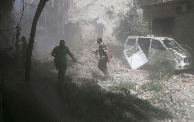 LUFTANGREP: Innbyggere ser på ødeleggelsene etter at syriske regimestyrker bombet byen Douma fredag.