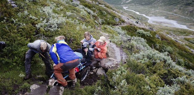 LAGARBEID: Fire personer må trekke Jacobs rullestol opp den bratte stigningen. Turkameratene er fornøyde med kvaliteten på begynnelsen av stien. Her får de til å trille vogna og løfte den over de steinene som er i veien.