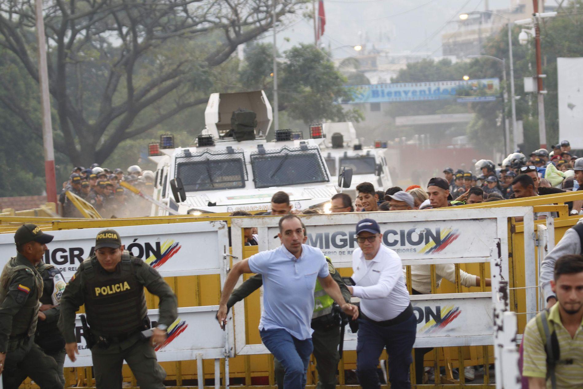 SKIFTET SIDE: Desperate mennesker løp bort idet fire soldater i to armerte biler satte opp farten og styrte mot grensesperringene mellom Venezuela og Colombia. Soldatene skal deretter ha gått over til opposisjonens side. Foto: AFP'