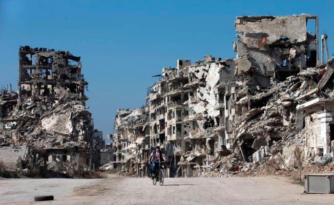 STORE ØDELEGGELSER: En syrisk gutt sykler her gjennom gamlebyen i Homs torsdag.