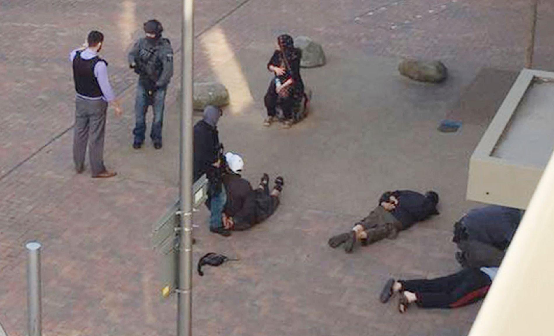 ARRESTERT: Her er flere av de arresterte i Barking lagt i jern på bakken. Et medlem av politiets innsatsstyrker står i bakgrunnen.