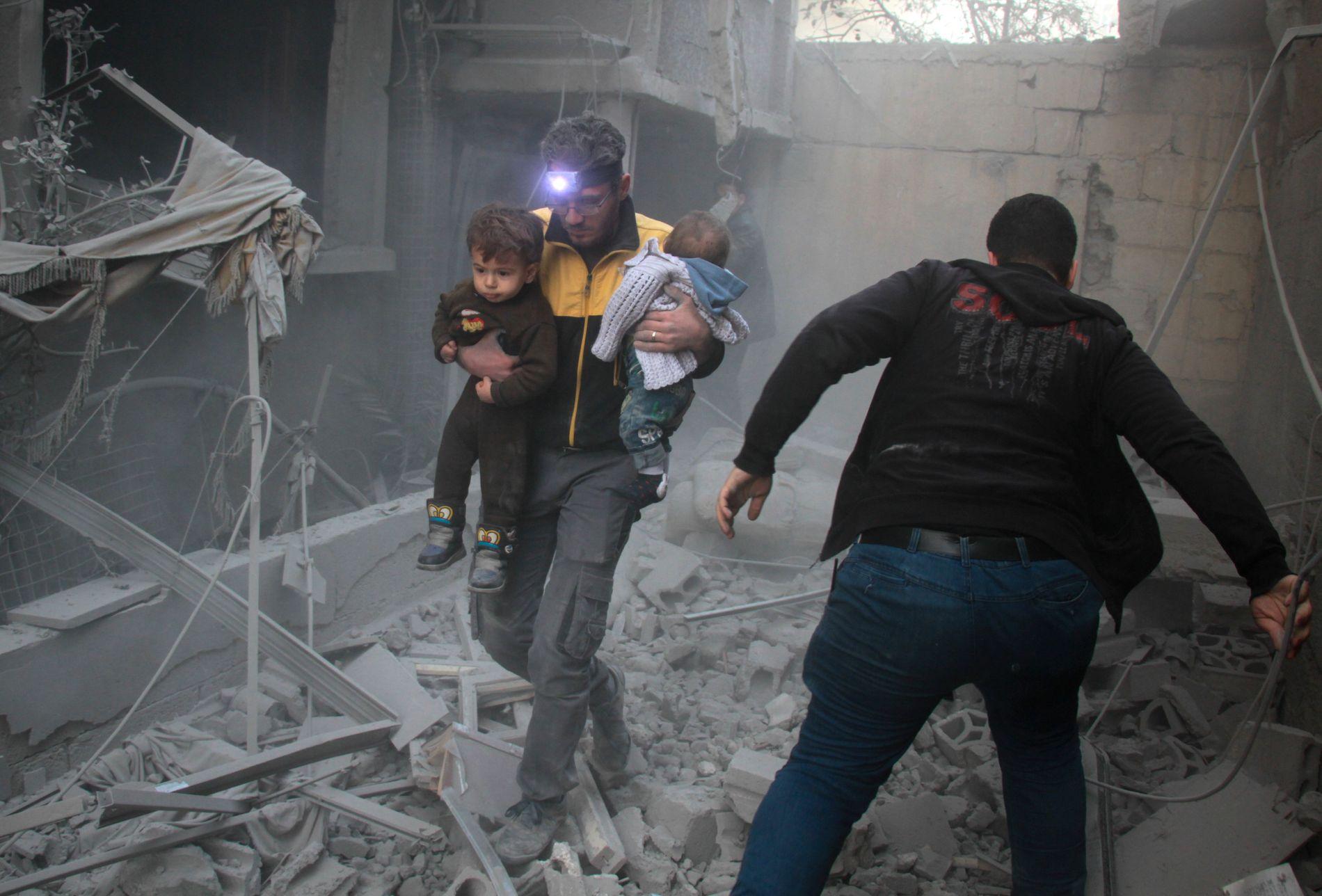 KRIG MOT BARN: En mann bærer to små barn ut av ruinene av en bygning som er truffet i et flyangrep mot den opprørskontrollerte byen Douma i det østlige Ghouta, utenfor Damaskus 7. februar. Syria er et av verdens farligste land for barn.