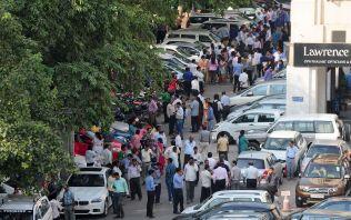 EVAKUERTE: Ansatte i dette bygget i New Delhi måtte evakuere til parkeringsplassen utenfor da et jordkjelv rammet India.