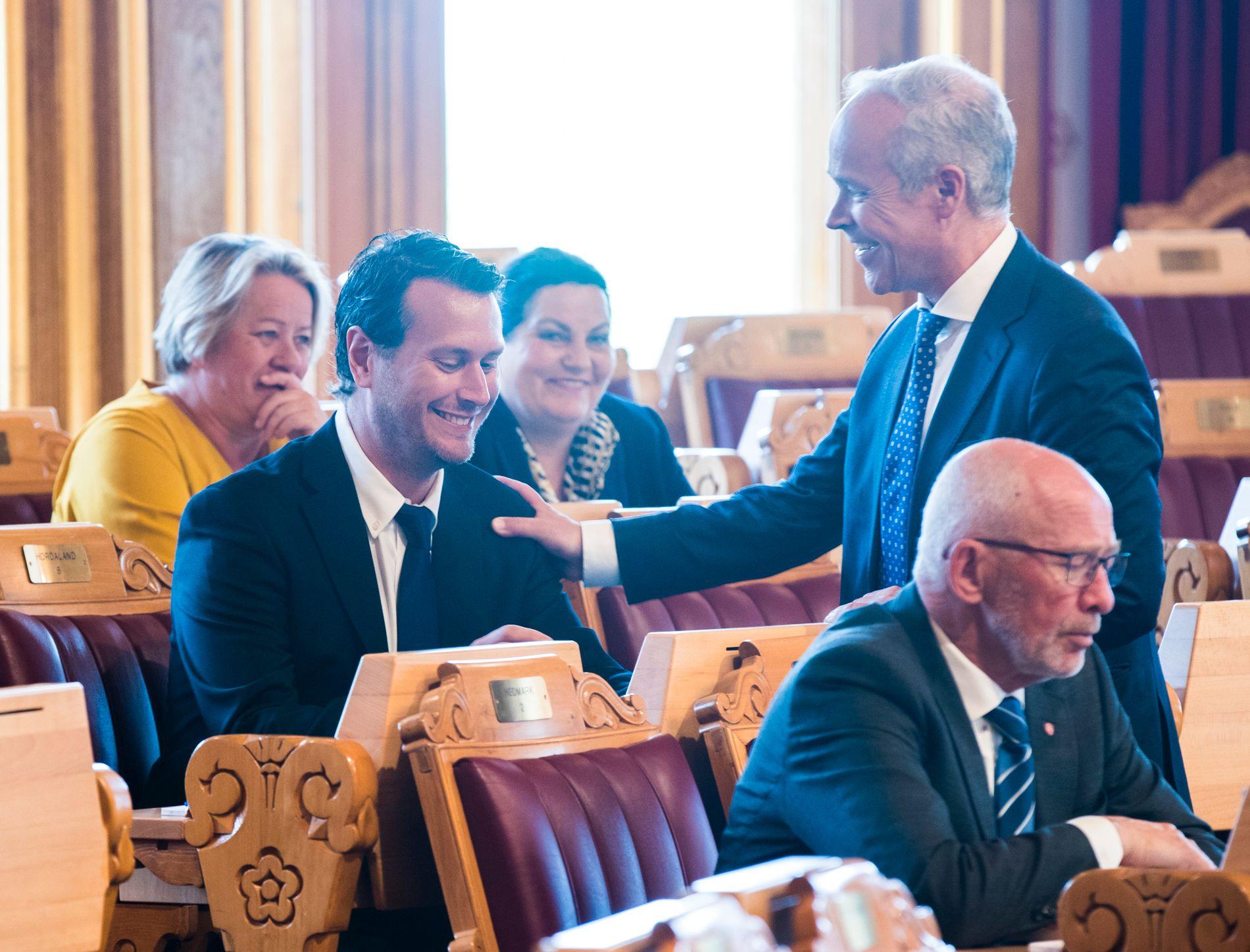 KOMMUNE-KAMERATER: Helge André Njåstad (Frp) får en klapp på skulderen av kommunalminister Tore Sanner (H) mens Stortinget behandler tvangssammenslåingene. Njåstad ledet forhandlingene om tvangssammenslåingene.