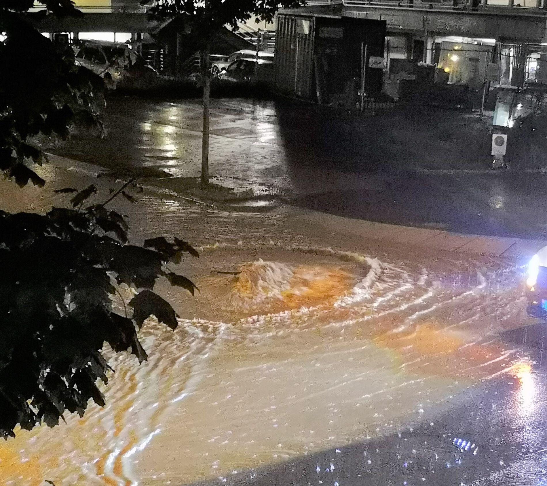 FOSSER UT: Vannet fosser ut fra et kumlokk midt i Brumunddal sentrum, i Ringsaker kommune, etter kraftig regnskyll.