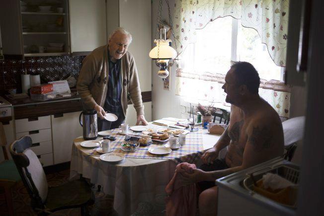 TO GODE NABOER: Odd Gunnar Smette (85) i Nybergsund byr nabo Jørn Heggbranna (45) på kaffe og kaker etter å ha fått hjelp til å fjerne ting fra kjelleren. Sistnevnte har vrengt av seg våte klær etter å ha vasset rundt i kjelleren. Foto: Kyrre Lien