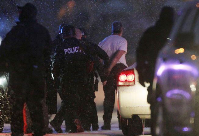 PÅGREPET: En mann føres bort fra abortklinikken i håndjern etter å ha overgitt seg til politiet. Det er uklart hva slags skytevåpen han brukte i angrepet der tre personer ble drept.