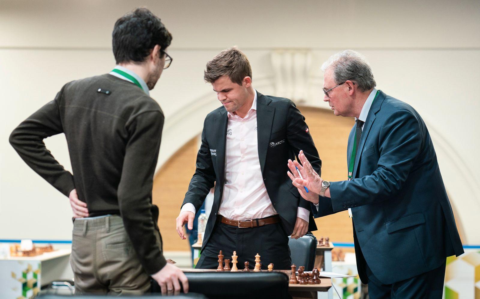 Magnus Carlsen oppgitt etter at han har tapt på tid for ukraineren Adam Tukhajev (med ryggen til). Dommerer er Igor Bolotinskij.