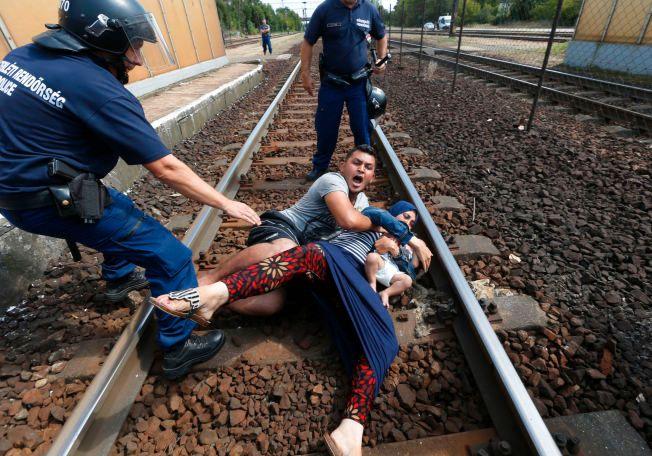 PÅ SKINNEGANGEN: Ungarsk politi prøver å få opp en syrisk flyktningfamilie som har lagt seg ned på skinnegangen i den ungarske byen Bicske.