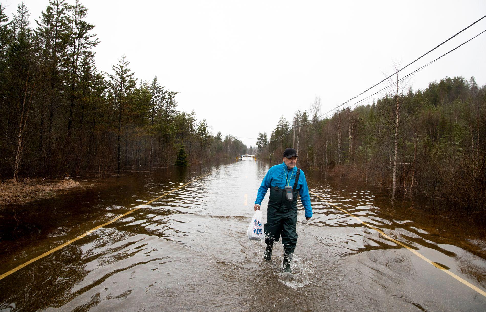 VASSER PÅ STENGT VEI: Rolf Hagen tok lørdag på seg vadebukse for å levere matvarer til en eldre mann som bor innenfor der veien er stengt få Fylkesvei 26 ved Nybergsund.