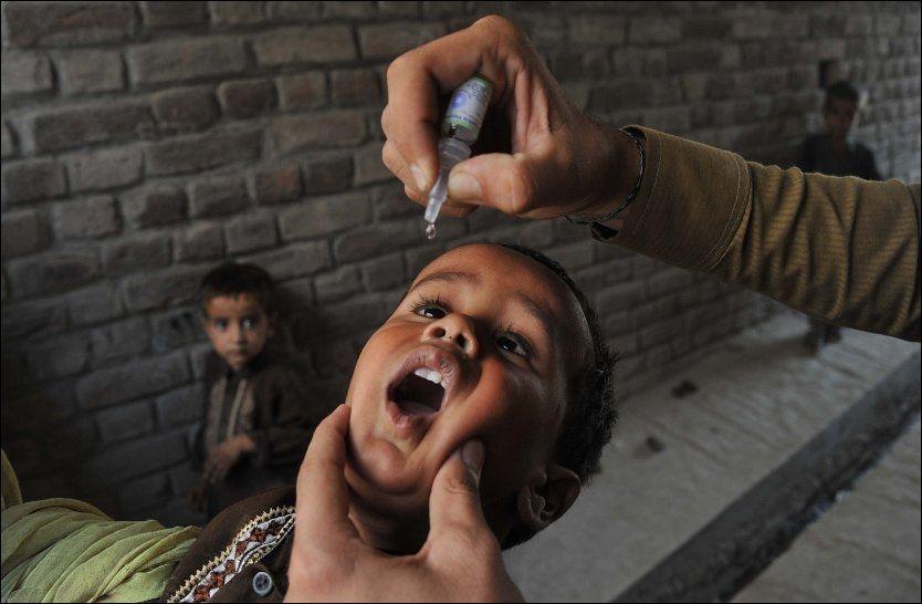 FARLIG: Det er ikke barnet som er mest utsatt her, men helsearbeideren som gir det poliovaksine er i fare. Foto: AFP