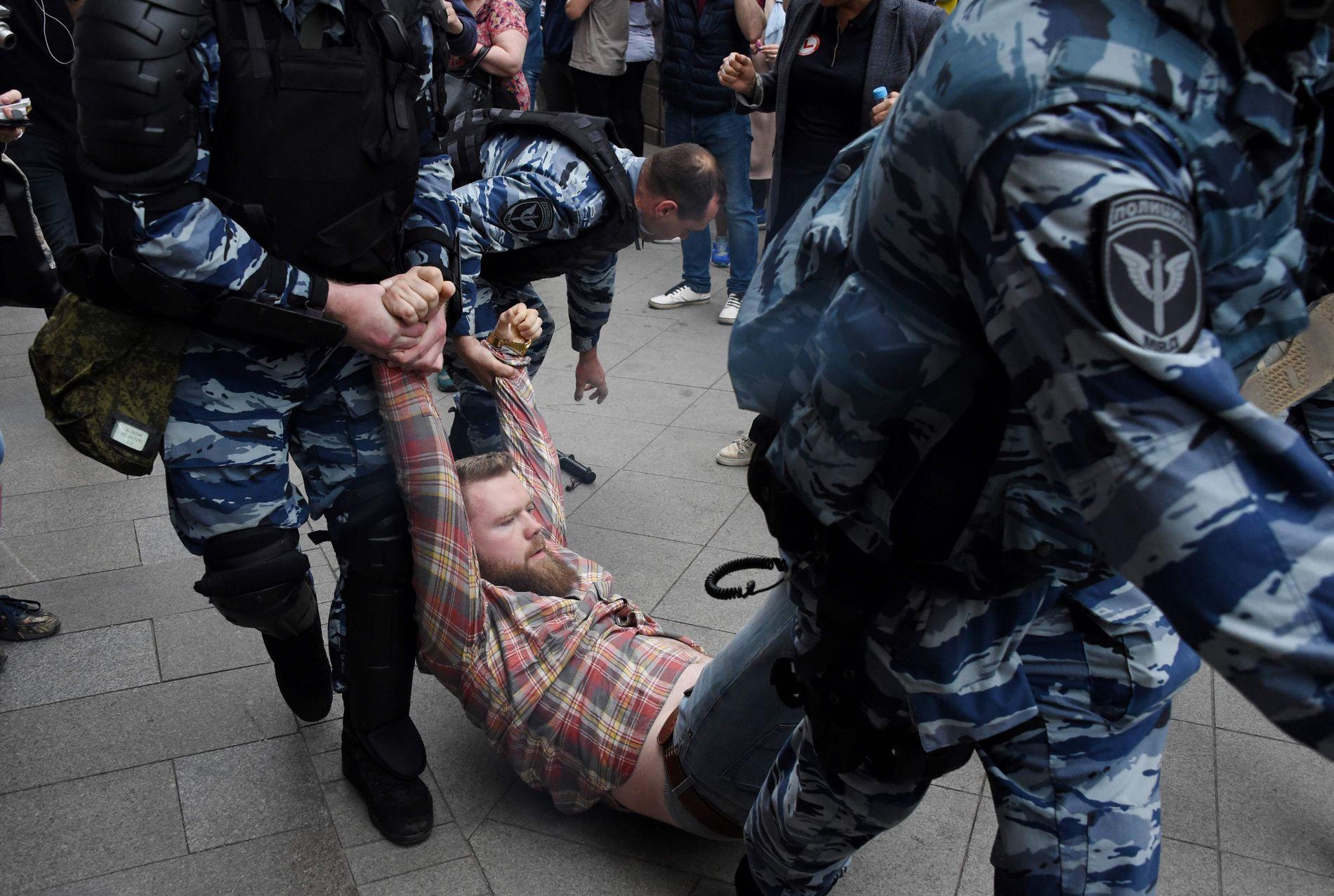 SAMMENSTØT: Russisk politi fjerne flere hundre av de 5000 demonstrantene på hovedgaten Tverskaya i Moskva mandag. FOTO: AFP