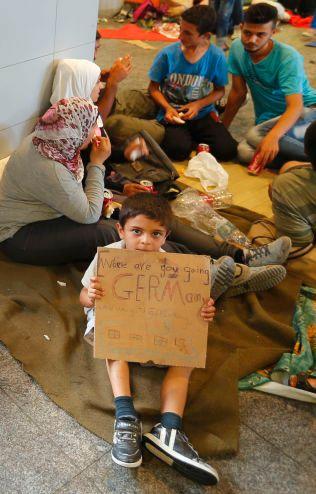 PÅ VEI: En liten gutt holder opp en plakat med påskriften «vi skal til Tyskland» utenfor jernbanestasjonen i Budapest.