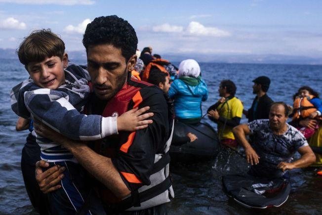 FORTSETTER Å KOMME: En mann redder i land et barn som ankom, den greske øya Lesvos tirsdag denne uken.