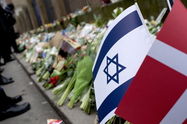 BLOMSTER OG FLAGG: Mange har lagt ned tulipaner, flagg og minneord utenfor synagogen de siste dagene.