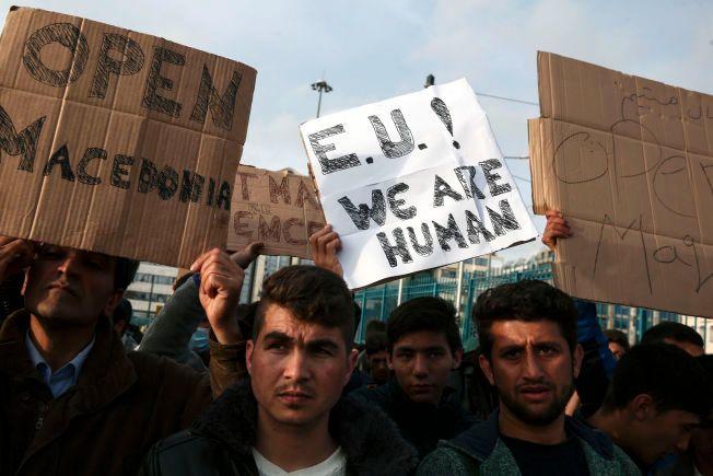 DEMONSTRERER: Flere flyktninger holder opp plakater med beskjer til EU i forkant av toppmøte mandag.
