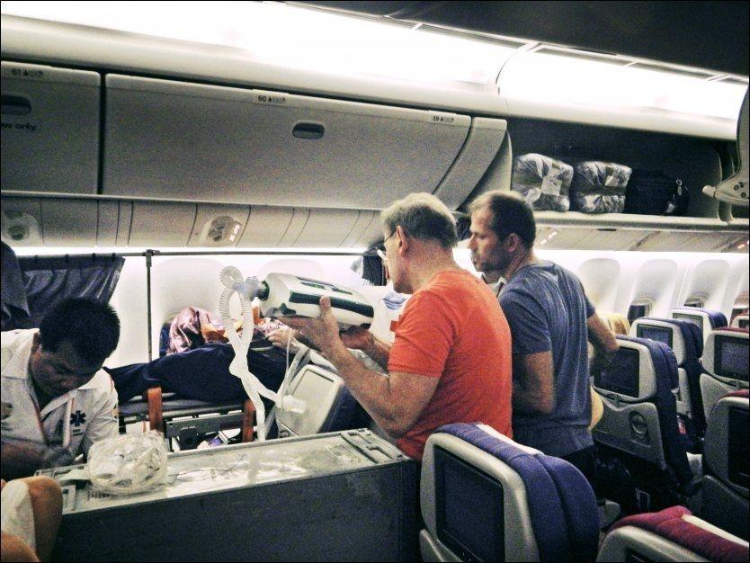 HJELPER NORDMENN: Lege Terje Erlid (i rød t-skjorte) og anestesilege Marius Filtvedt passer på at den norske respiratorpasienten fraktes trygt til Norge ombord på Thai Airways-flyet fra Bangkok til Oslo. Bildet er tatt i fjor høst. Foto: PRIVAT
