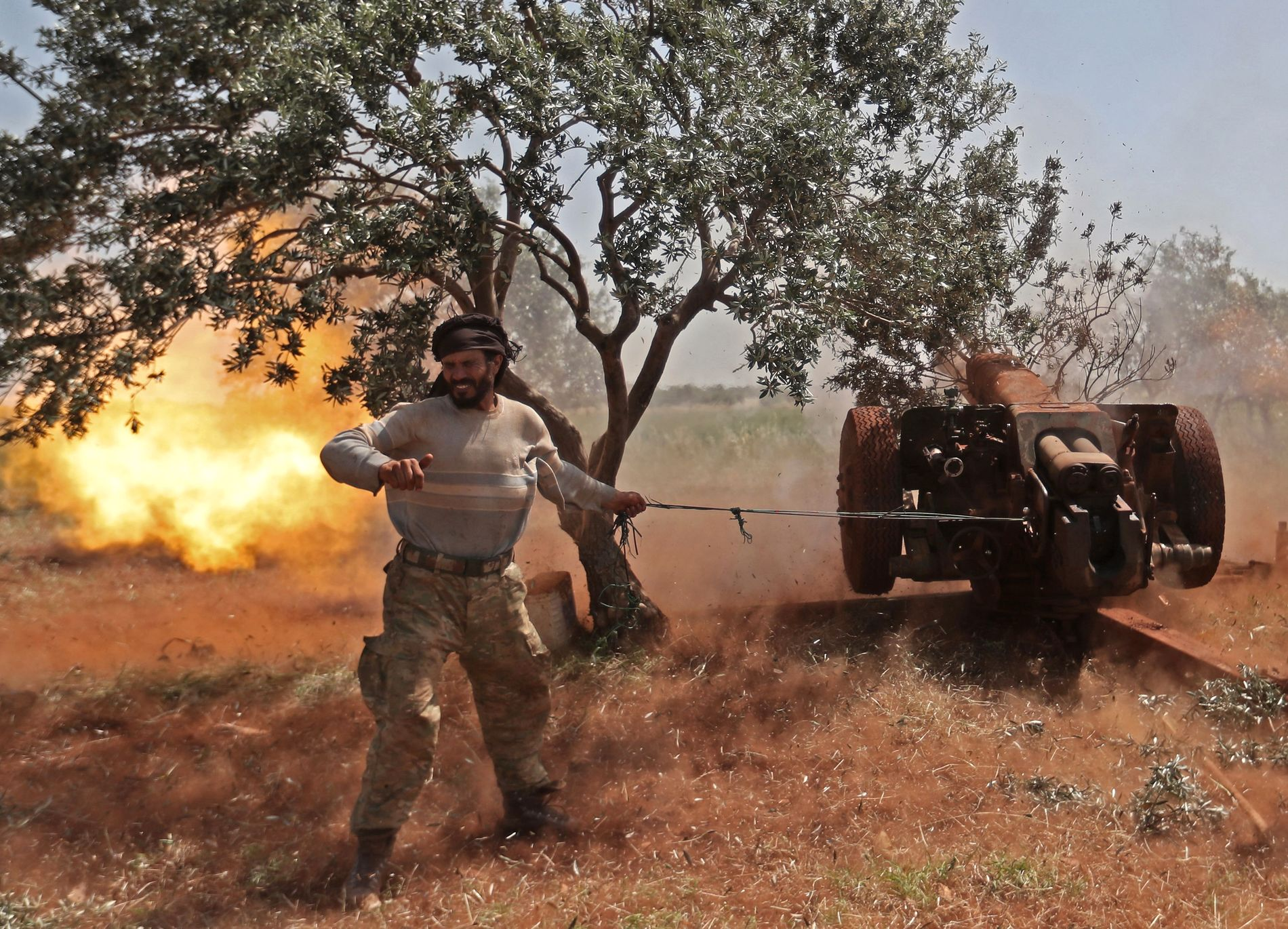 BAKKEKRIG: En kriger i den tyrkisk-støttede opprørsgruppen National Liberation Front (NLF) fyrer mot regimestillinger i Idlib i mai.
