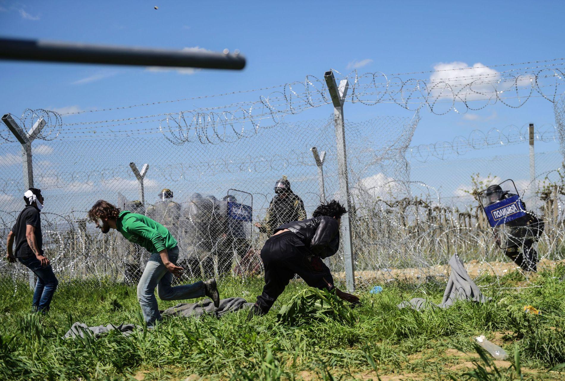 VOLDSOMT: Migranter forsøker å bryte seg gjennom gjerdet.