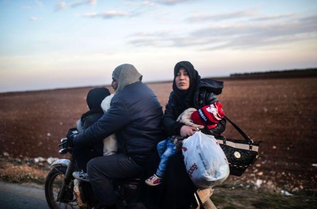 TITUSENER PÅ FLUKT: 20.000 personer har de siste dagene flyktet til grensen mellom Syria og Tyrkia, hvor det fra før befinner seg 30.000 mennesker. Her flykter en syrisk familie på motorsykkel fra Bab-Al Salama fredag denne uken.