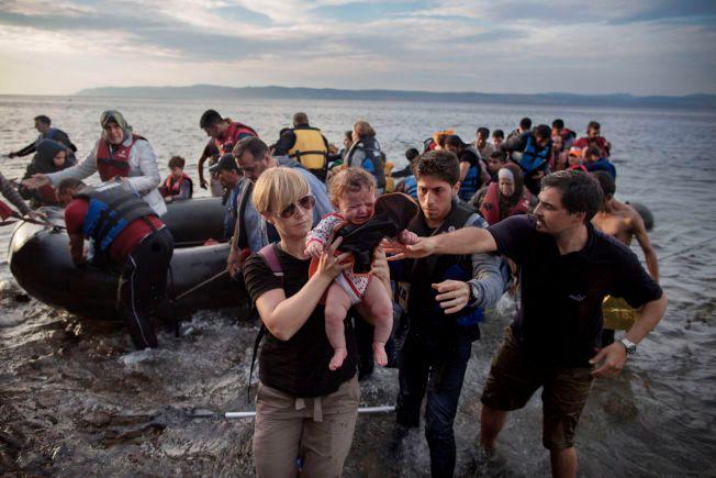VENTER MANGE NYE: Her på stranden i greske Lesvos kommer mange stappfulle gummibåter i land. Norske Monica Nyborg tar hånd om et lite syrisk barn som har kommet med sin familie og andre flyktninger. Hver dag anslås det at det ankommer rundt 2.000 flyktninger til den greske ferieøya.